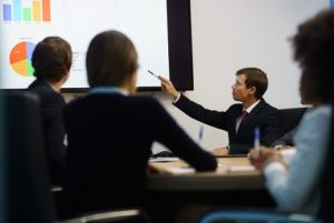 Group of business people meeting in corporate conference room, smiling during a presentation. The coworkers are examining charts and slides on a big TV monitor