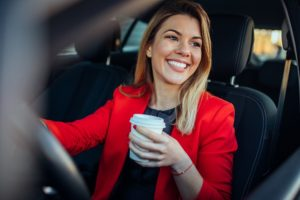 Photo of a smiling business woman in the car drinking coffee.
