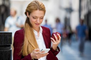 Young business woman sitting on the city street with smartphone and eating big red apple on lunch break. Texting and smiling. Happy businesswoman working on smart phone. healthy lifestyle, .
