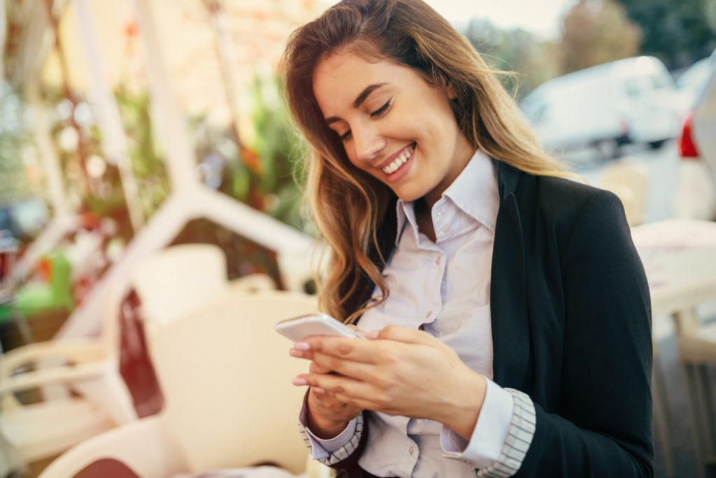Happy businesswoman using phone outdoors