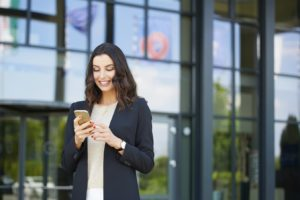 Shot of a smiling young businesswoman text messaging while standing outdoor on the street.