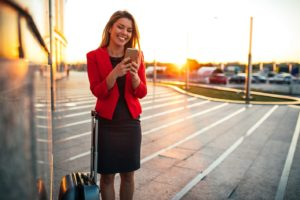 Portrait of a traveling business woman using mobile phone in the airport at sunset.