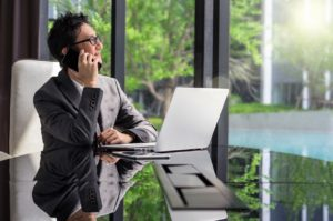 Happy young asian businessman sitting on working space and using cell phone and laptop. business communication concept