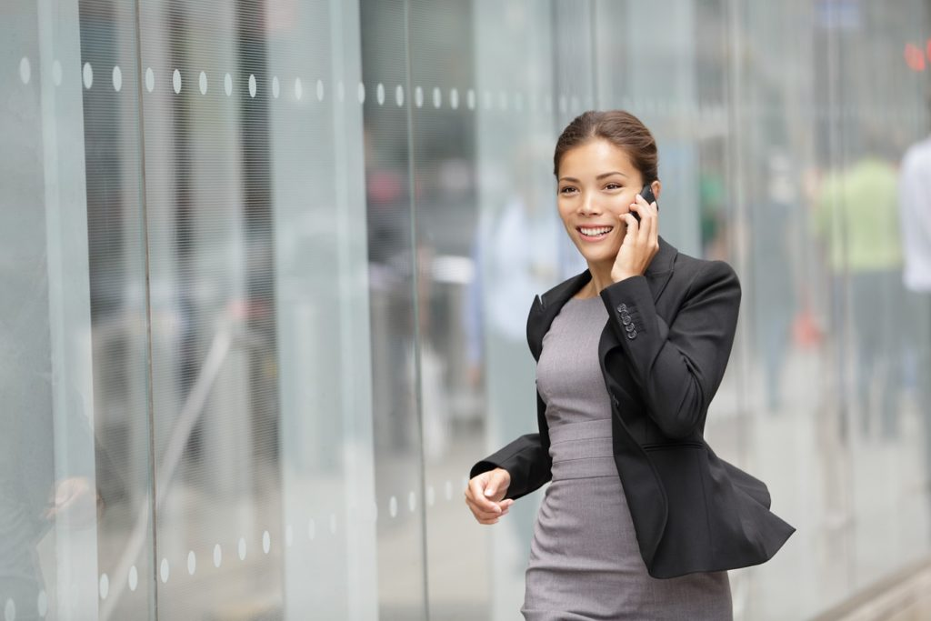 Businesswoman on cellphone running while talking on smart phone. Happy smiling mixed race Asian / Caucasian business xwoman busy. Image from Manhattan, New York City. Click for more: